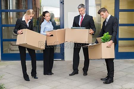 unhappy geschaeftsleute mit kartons ausserhalb des