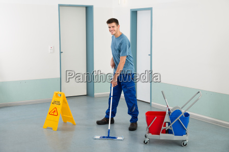 maennlicher arbeiter mit reinigungsmitteln mopping boden
