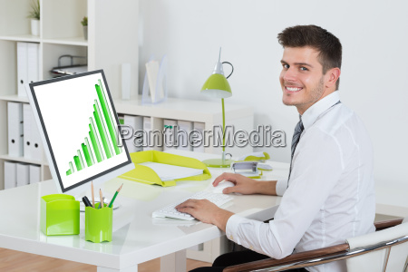 young businessman analyzing graph on computer