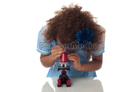school girl using microscope