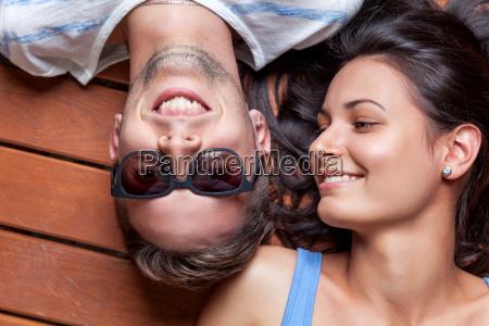 glueckliches junges paar auf einem holzboden