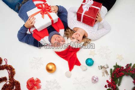 reizende weihnachtspaare mit geschenken liegen