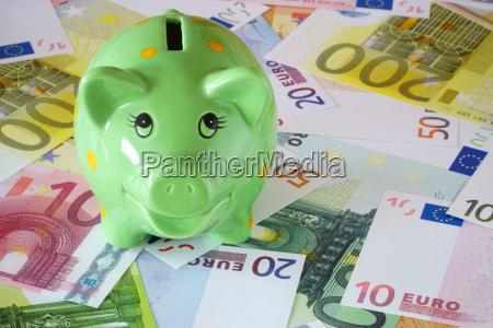 gruenes sparschwein und euro geldscheine zum