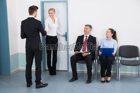 businesswoman shaking hands with man in