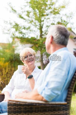 senior mann und frau sitzen vor