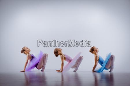 drei kleine maedchen in ballettroeckchen sitzen