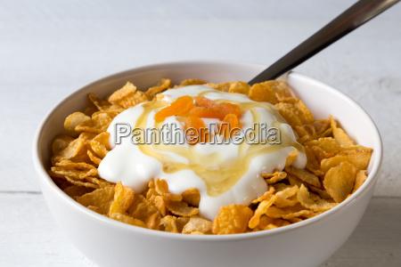 cornflakes in einer schale mit joghurt