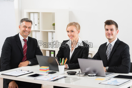 group of businesspeople sitting at desk
