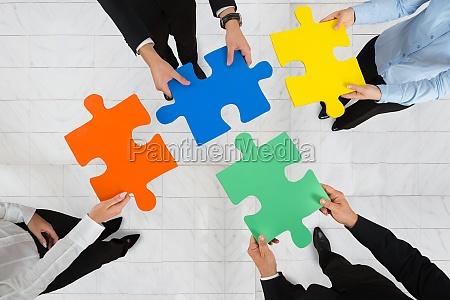 geschaeftsleute halten puzzle pieces