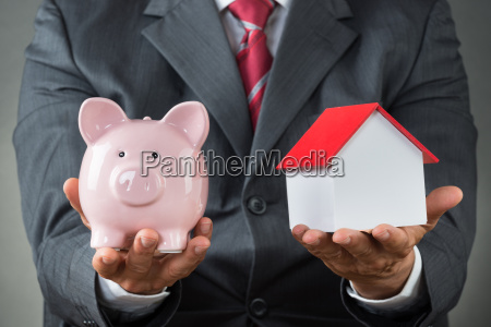 businessman holding piggy bank and house