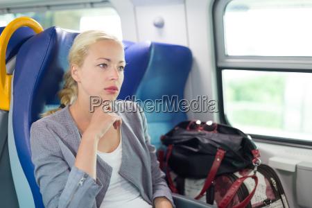 blonde geschaeftsfrau die mit dem zug