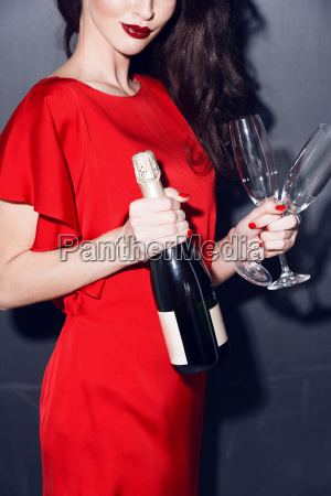 woman in red dress wich champagne