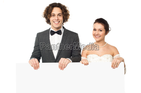 young married couple holding blank whiteboard