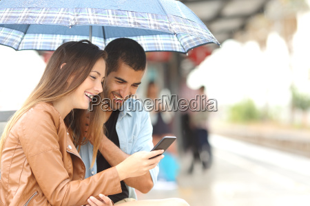 interracial couple sharing a phone in