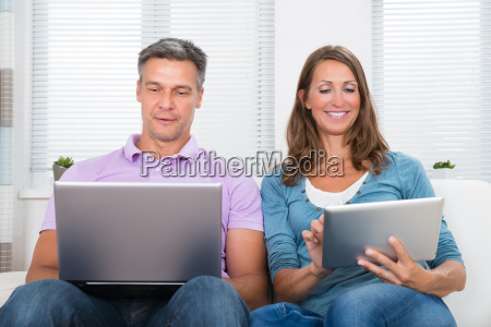 couple with laptop and digital tablet