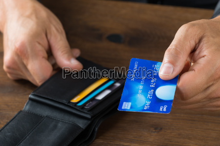 businessman giving credit card from wallet