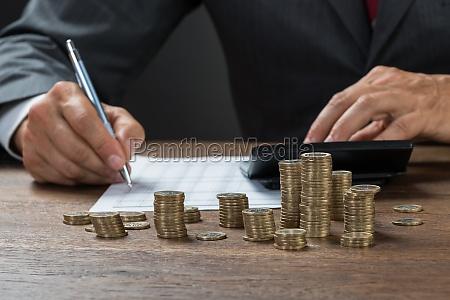 accountant calculating profit mit muenzen auf
