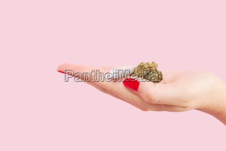 woman holding cannabis bud