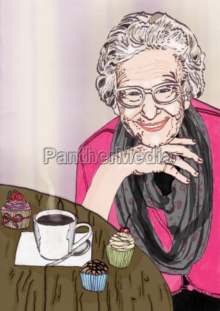 freundliche oma sitzt am tisch mit