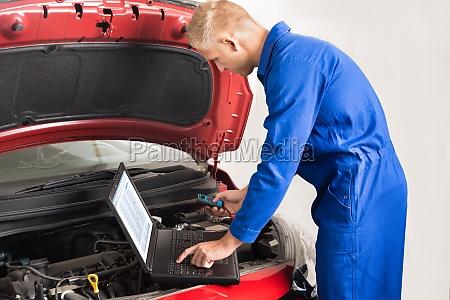 mechaniker nutzen laptop waehrend der reparatur