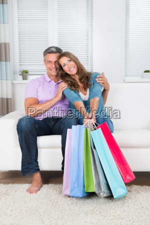 couple with shopping bags sitting on