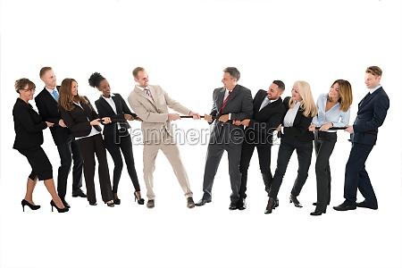 multi ethnic business teams playing tug
