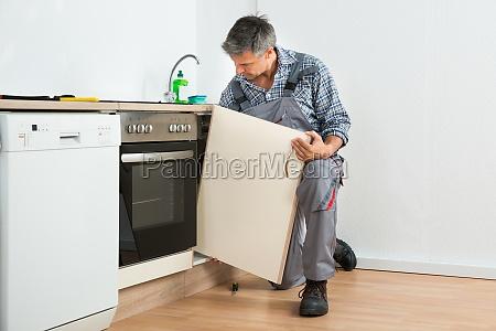 handyman fixing sink tuer in der