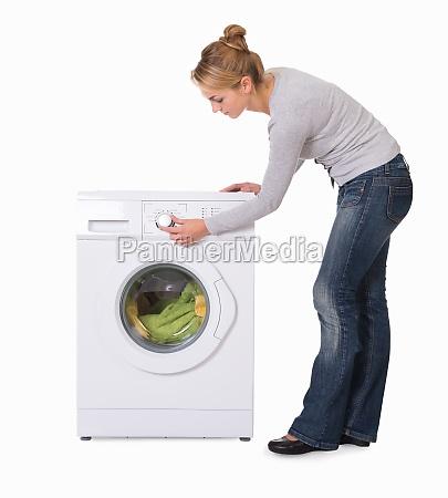 woman using washing machine over white