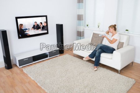 woman watching tv while sitting on