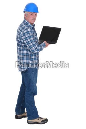 senior worker holding laptop