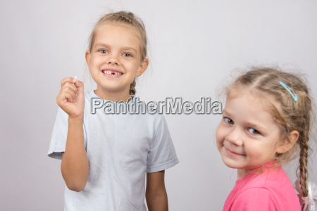 girl holding a fallen front tooth