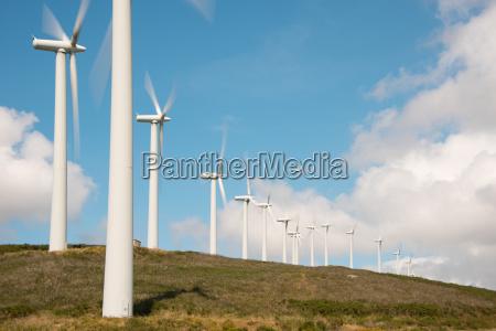 windkraftraeder in windpark auf huegelkette in