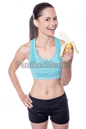 young female trainer eating banana