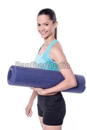 female trainer holding exercise mat
