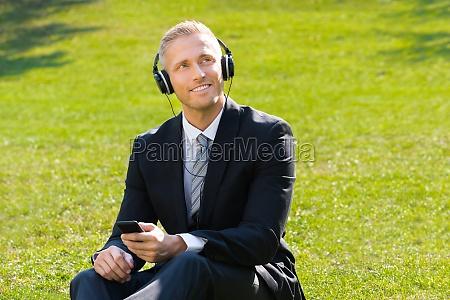 geschaeftsmann hoert musik im park