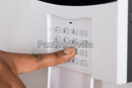 persons hand entering code in security