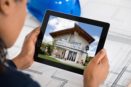 woman holding digital tablet over blueprint