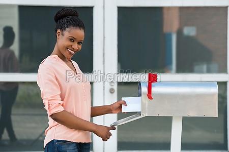 frau sammeln ihre post von mailbox
