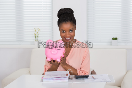 woman holding piggybank with eyeglasses