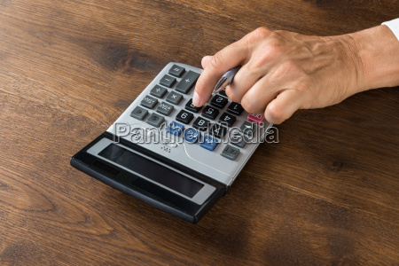 businessman using calculator at desk