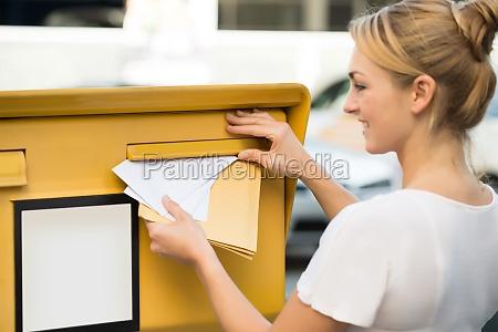 frau die brief in postfach einfuegt