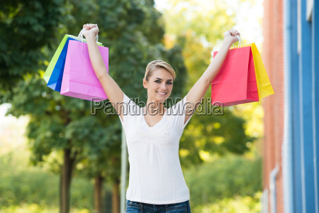woman with arms raised carrying shopping