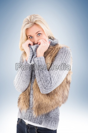 blonde in winter clothes smiling at