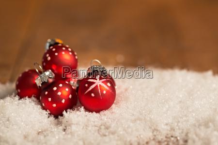 rote weihnachtskugeln im schnee weihnachten