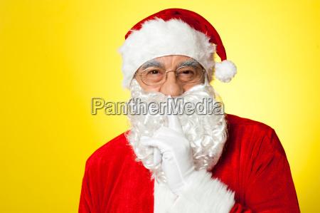 santa showing finger on lips sign