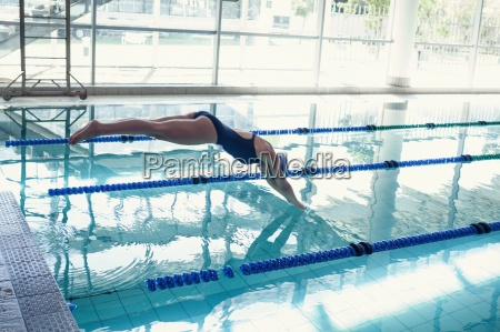 side view of swimmer diving into