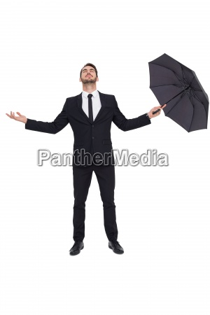 businessman with arm out holding umbrella