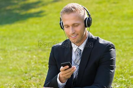 geschaeftsmann hoert musik in park