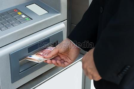 person geld von geldautomaten maschine