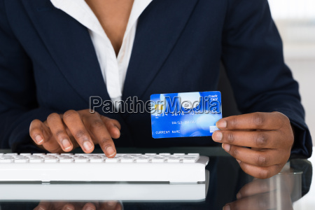 persons hand holding credit card while